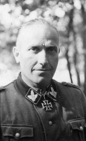 Black-and-white portrait of a man wearing a military uniform with an Iron Cross displayed at his neck.