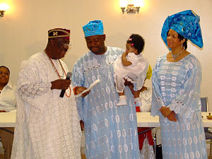 An Igbo couple standing with the dad holding a what looks to be a girl child in a naming ceremony, a man known as di okpara or the head of the family, standing left, checks the names with the couple looking one. The wear blue lace outfits and the di okpara wears white. The baby wears white, the woman wears a blue head tie and the father a blue cap, the di okpara wears a red cap