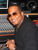 An Afro-American man is smiling. He is sitting in a control room, which includes a mixing console and monitor speakers. He wears sunglasses, a black shirt and a wristwatch.