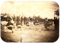 An old photograph showing a procession passing between lines of soldiers with tents in the background