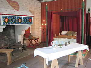 On the left is a fireplace with various heraldic arms painted on it, on the right is a four-post bed, and in the front is a set table on trestles. The floor is wooden and the walls are covered with painted patterns and drapes.
