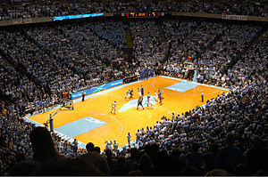 The inside of a basketball dome with two teams on a court with a large logo in the shape of the state of North Carolina in the middle.