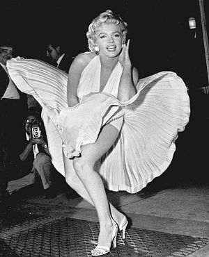 Monroe is posing for photographers, wearing a white halterneck dress, which hem is blown up by air from a subway grate on which she is standing.
