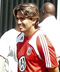 A Hispanic soccer player with shiny brown hair smiles and faces left. He is wearing a red jersey with white and black details and a VW logo.