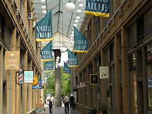 "Atrium of a shopping arcade, with green and yellow banners hanging overhead with the words ""Nickels Arcade"""