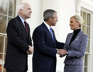 White-haired man in dark suit looks on as grey-haired man in dark suit holds hand and greets blonde-haired woman in medium-colored suit, all in front of a white building.