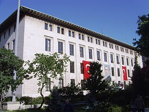 A four-story, white flat-roofed building with two Turkish flags and a portrait on the exterior