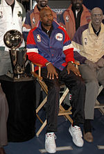 A man, wearing a black shirt and blue-red jacket with the logo NBA on it, is sitting on a chair while posing for a photo. He is surrounded by four other men, while a gold trophy is placed on his right.