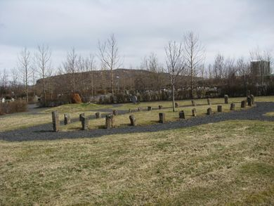 A grassy area with stones arranged in an oval shape demarcating a burial area. In the distance can be seen trees and a hill.