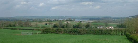 View of Chew Valley Lake in the distance with green farmland in the foreground and hills in the distance