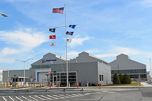 Boeing plant in Ridley Park, Pennsylvania - a building with aluminum siding, parking lot in front, and a flagpole with seven flags