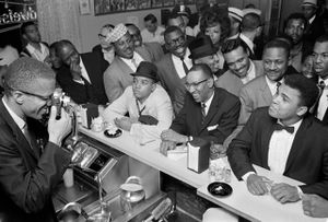 Malcolm X is holding a camera and taking a picture of Clay, who is sitting at a luncheonette counter