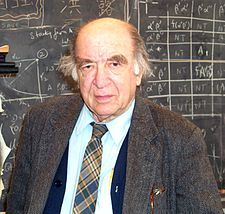 chest high portrait in suit and tie with longish hair in front of blackboard calculations