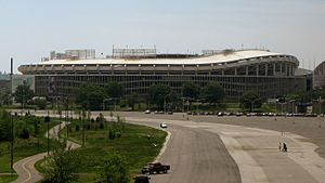 A large circular stadium with a curving overhang behind a mostly unused parking lot.