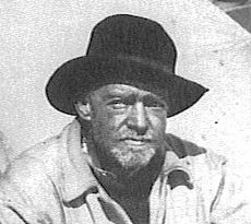 Head and shoulders of an unshaven man in dark, wide-brimmed hat, weatherbeaten face looking directly at the camera
