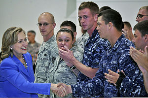 Clinton greeting U.S. military personnel at Andersen Air Force Base in Guam. The personnel are wearing uniforms and standing side-by-side.