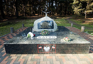 "A large rock set on a pedestal of polished stone. On the pedestal, the words ""Katyn Memorial"" are visible. On the rock, a plaque reads ""In memory of 25,000 Polish prisoners of war and professional classes who were murdered on Stalin's orders by the Soviet Secret Police in 1940 at Katyn Forest, Kharkov, Miednoye, Kozielsk, Starobielsk, Ostaszkov and elsewhere. Finally admitted in 1990 by the USSR after 50 years of shameful denial of the truth."""