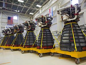 Six rocket engines, consisting of a large bell-shaped nozzle with working parts mounted to the top, stored in a large warehouse with white walls decorated with flags. Each engine has several pieces of red protective equipment attached to it and is mounted on a yellow wheeled pallet-like structure.