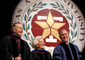 "The head and shoulders of three people – an older man, an older woman, and a middle-aged man – wearing formal robes are shown in front of a large circular seal. On the outer edges of the seal the letters ""XAS A...IVERSITY...87..."" are visible; an inner band of leaves separates the letters from a block T superimposed with a star."