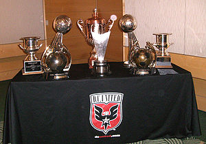 A table holding seven golden trophies of various sizes. The table is cover by a cloth with the team's shield on it.