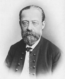 Portrait of balding, bearded, bespectacled middle-aged man with solemn expression, wearing a bow tie and high-buttoned jacket