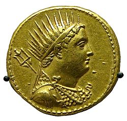 A gold coin shows the profiled bust of a man. The man is wearing a crown and drapery.
