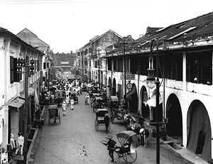 High angle view of a street lined with two and three story structures. The street is filled with crowds, including horse-drawn and hand-pulled carriages.