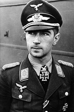The head and shoulders of a young man, shown in semi-profile. He wears a field cap and a pilot's leather jacket with a fur collar, with an Iron Cross displayed at the front of his shirt collar. His hair is dark and short, his nose is long and straight, and his facial expression is a determined and confident smile; his eyes gaze into the distance.