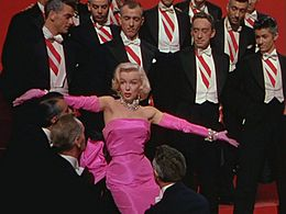 Monroe in Gentlemen Prefer Blondes. She is wearing a shocking pink dress with matching gloves and diamond jewellery, and is surrounded by men in tuxedos.