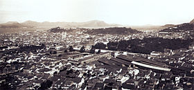 Photograph looking down over the rooftops of a large city with hills and a waterway in the far distance