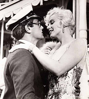 Monroe in Some Like It Hot. Monroe is wearing a dress with sequins and a fur stole and embraces Tony Curtis, who is wearing a jacket and a sea captain's hat.