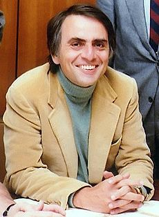 Color photo. Man sitting wearing a suit and smiling.