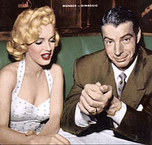 Monroe wearing a white polka-dot dress and sitting next to Joe DiMaggio in a restaurant-type setting