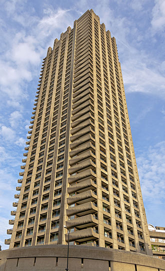 A tall concrete tower, with projecting balconies on the corners, viewed from below its lowest level. It is lit from behind and above by gold-tinges late afternoon sunlight. The sky behind it is blue with thin clouds.