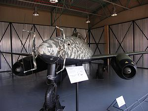 "A twin engine jet aircraft pictured from front-left sitting on the ground in a hangar. The paint scheme of the aircraft is camouflage of various brown and green colours. Two antennas are protruding from the nose of the aircraft. The white number ""305"" is visible on the nose of the aircraft."