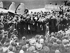A large crowd on an airfield; British Prime Minister Neville Chamberlain presents an assurance from German Chancellor Adolf Hitler.