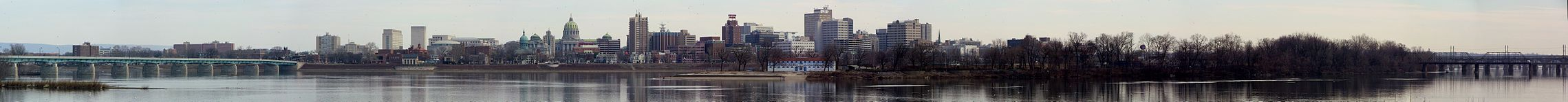 A city skyline, including the Pennsylvania State Capitol, beyond a river with bridges extending across the river on both sides of the photograph. An island is prominent in the right mid-ground.