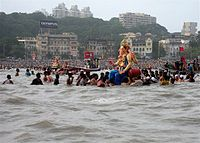 Large statue of Ganesha on the water, surrounded by people