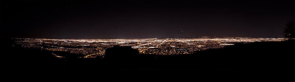 The Phoenix skyline at night from South Mountain. Almost everything in the foreground is darkened, but there are lights in the center and the background, which delineate streets and buildings.