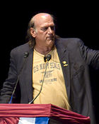 Balding man with long hair, T-shirt and jacket at podium.