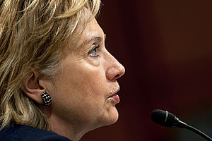 Side profile of Clinton facing toward her right side. She is speaking into a microphone.