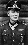 A man wearing a military uniform and peaked cap with an Iron Cross displayed at the front of his uniform collar.