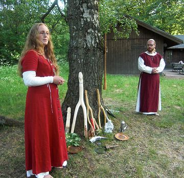 A man and a woman stand outdoors by a tree, wearing red and white robes.