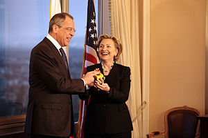 "Hillary Clinton standing with Russian Foreign Minister Sergey Lavrov. Both of them are holding a ""reset button"". They are in a room with a window to the left and an American flag behind them"