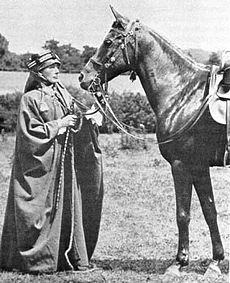 A black-and-white photograph of a European woman dressed in Bedouin robes and head covering, standing in front of a dark horse equipped with a bridle and saddle.