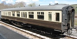 A long coach with domed roof ends. The roof is pale grey and ends black. The body has brown lower parts but cream above around the windows.