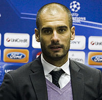 Josep Guardiola is seen in the picture. He is shown with a faded beard and hair wearing a suit.