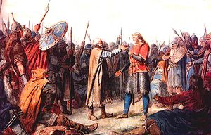A group of warriors in medieval garb surround two men whose postures suggest they are about to embrace. The man on the right is taller, has long fair hair and wears a bright red tunic. The man on the left his balding with short grey hair and a white beard. He wears a long brown cloak.