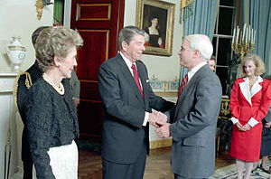 White-haired man in suit greets dark-haired man in suit in formal setting, as gaunt, well-coiffed woman looks on
