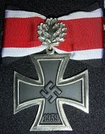A silver framed black cross that has arms which are narrow at the center, and broader at the perimeter. In the middle of the cross is a swastika, an equilateral cross with its arms bent at right angles. On the lower arm of the cross are the number 1939 engraved. The cross is connected to a ribbon with a silver clasp in shape of leaves. The ribbon has a red central stripe, flanked in white and with a black edge stripe.
